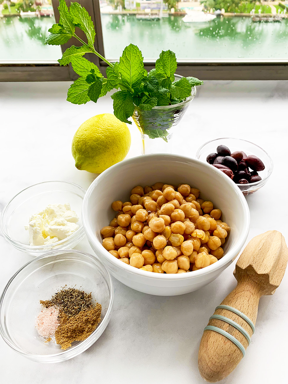 Greek Hummus made with feta cheese and kalamata olives. Add fresh mint, lemon juice and zest for a burst of fresh Mediterranean flavor.