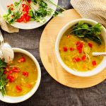 Bowls of Instant Pot Split Pea Chicken Soup with garnish of red peppers and parsley
