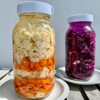 Fermented Cauliflower and Carrots with Grated Ginger and Garlic and Celery Seeds. Fermenting in a Mason Jar with Airlock Lid. Fermenting Sauerkraut in the background. Red Cabbage fermenting in a Mason jar