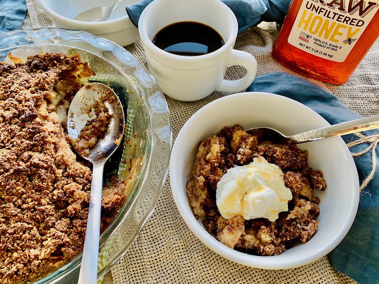 Apple Crisp topped with yogurt, honey, and next to cup of coffee