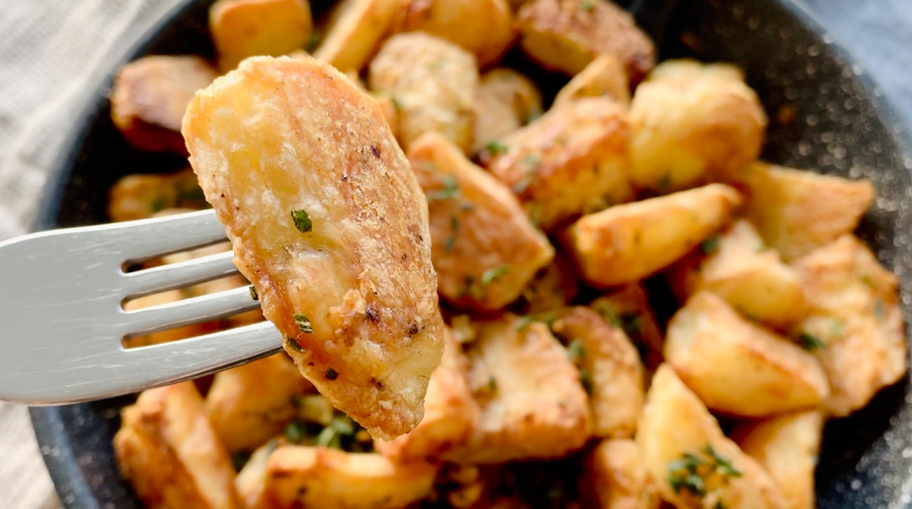 Fork spearing chunk of Crispy Roasted Potatoes with garlic and herbs