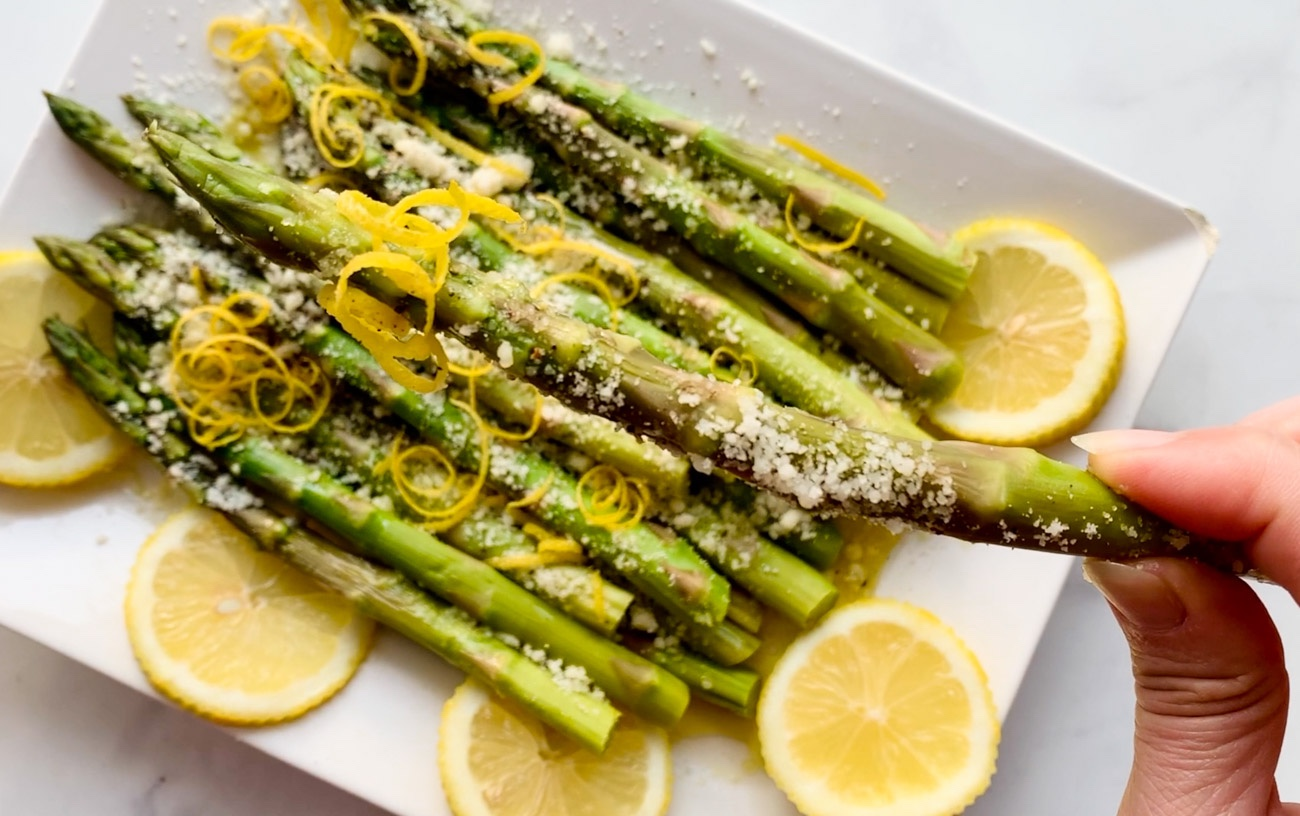 Platter with steamed asparagus, lemon and parmesan cheese