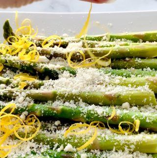 Lemon peel and parmesan cheese on steamed asparagus
