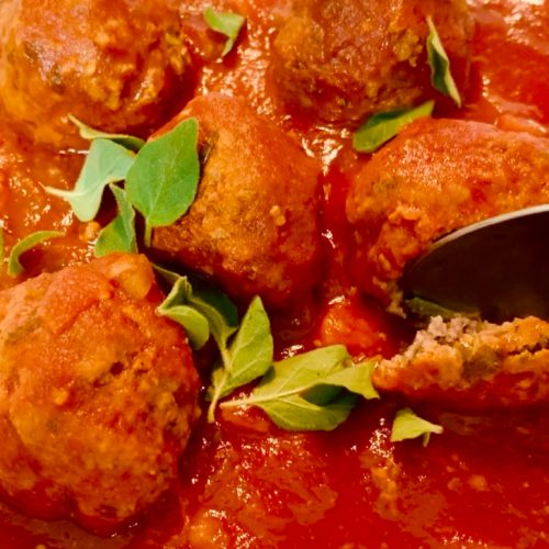 Spoon scooping up a meatball with tomato sauce