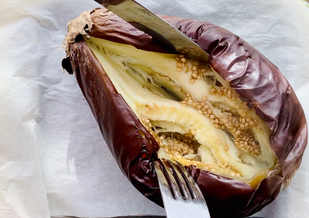 Cutting open a roasted eggplant