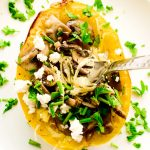 Fork in a spaghetti squash topped with mushrooms, feta cheese, parsley, thyme and chives