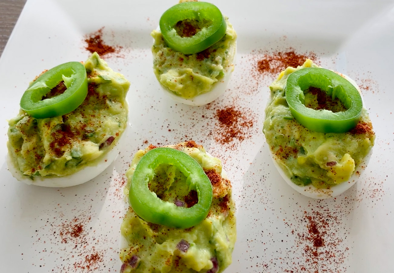 Jalapeno slices on top of deviled eggs with avocado